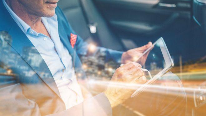 Homem com rosto não identificado mexe em tablet dentro de um carro