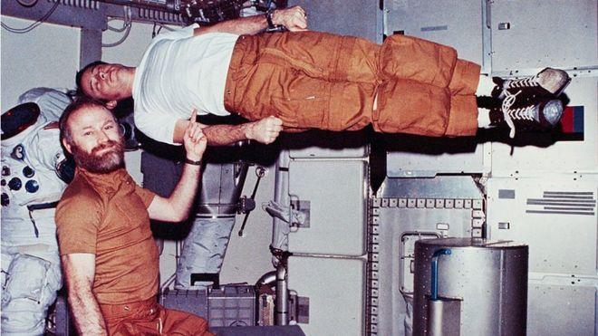 Jerry Carr finge sostener a un Ed Gibson que flota sin gravedad con un dedo.