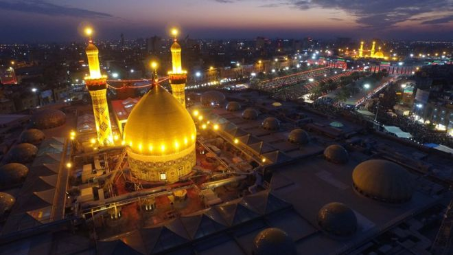 صورة جوية ليلية لمرقد الإمام العباس وفي الخلفية يبدو مرقد الإمام الحسين وسط مدينة كربلاء العراقية