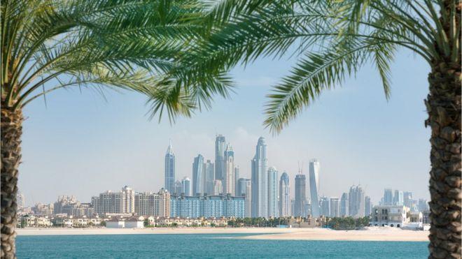 La marina de Dubái enmarcada por dos palmeras.