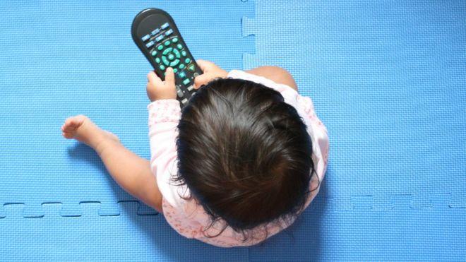 Una bebé con un control remoto de televisión.