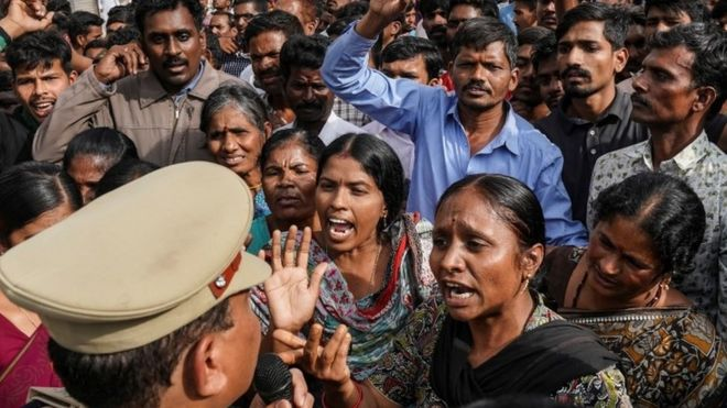 People argue with police over a protest against the alleged rape and murder of a 27-year-old woman