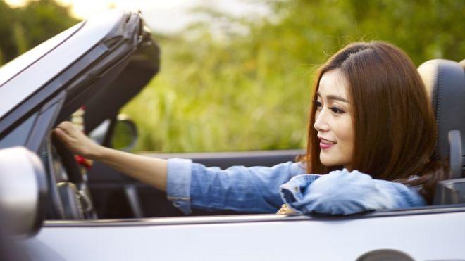 Mujer conduciendo un auto lujoso en Singapur