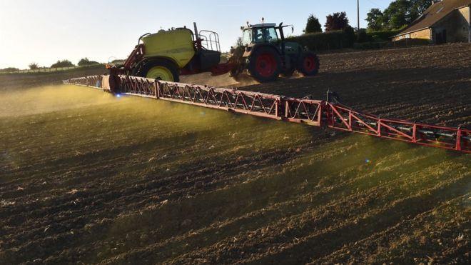 Trator pulverizando um campo