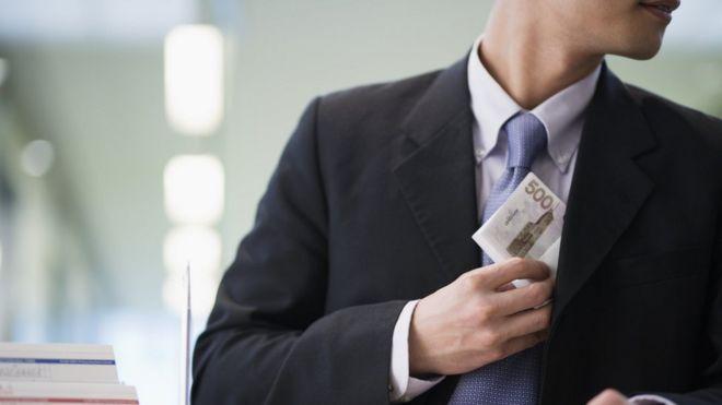 hombre de traje robando dinero