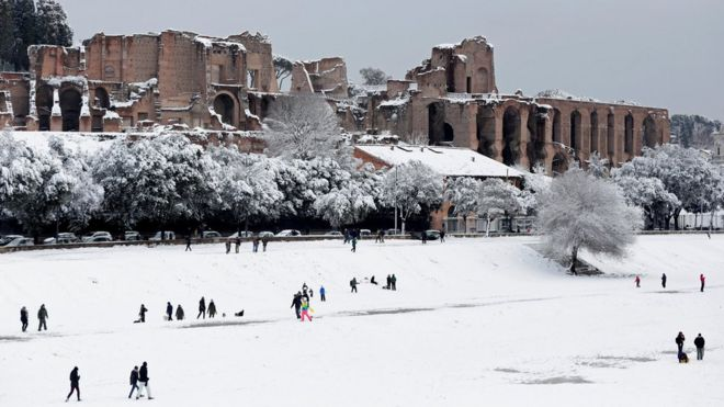 People walk during a heavy snowfall at the Circus Maximus in Rome