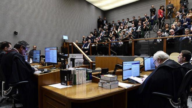 Quinta Turma reunida em julgamento no primeiro plano, e plateia em segundo plano