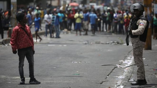 A man talks to a Haitian National Police officer guarding a commercial area that was looted during protests against fuel price increases in Port-au-Prince, Haiti, July 8, 2018.