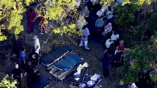 Los servicios de emergencia colocan camillas a la entrada de la residencia.