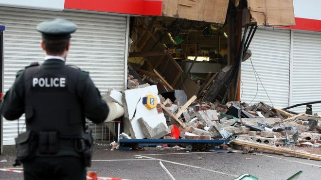 back of policeman in foreground, exploded ATM unit in background