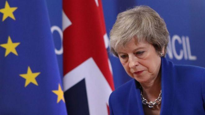 Theresa May em frente a bandeiras do Reino Unido e da União Europeia