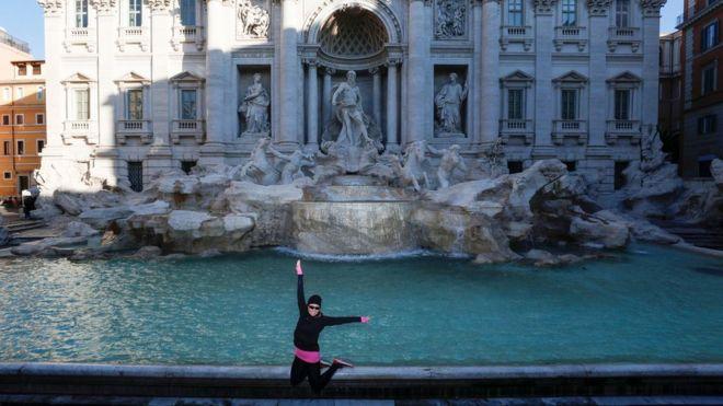Una mujer posa frente a la Fontana di Trevi en Roma.