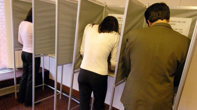 Избиратели в кабине для голосования