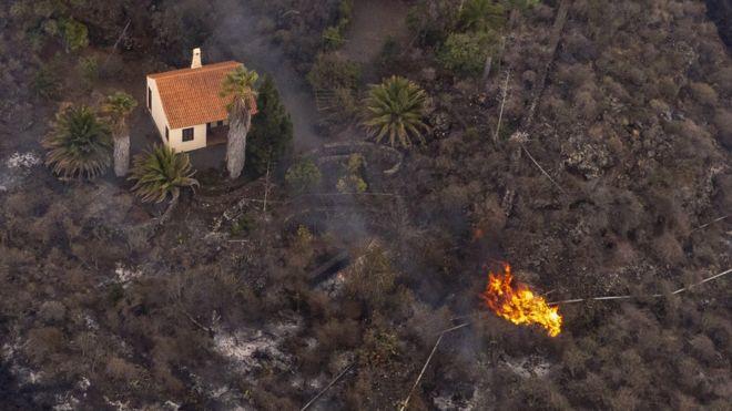 Foto aérea de una casa en pie rodeada por la lava en La Palma