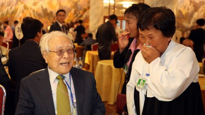 101-year-old Paek Seong-gyu (L) smiles as he meets his granddaughter Baek Yong-ok (R)