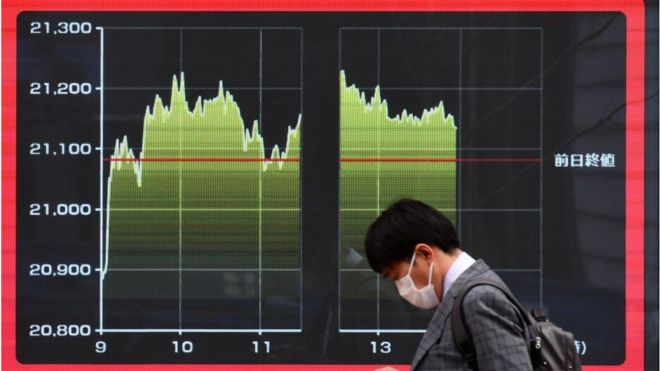 A pedestrian walks past a quotation board displaying a share price of the Tokyo Stock Exchange in Tokyo.