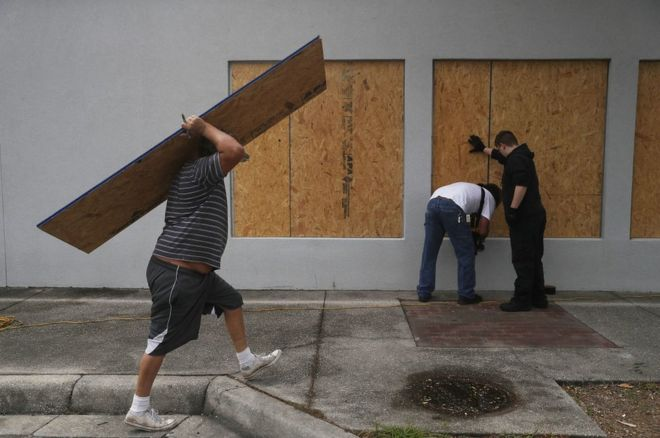 در فلوریدا مردم با تختههای چوبی در و پنجرهها را مسدود میکنند تا بلکه از ورود گردباد به داخل خانه جلوگیری کنند
