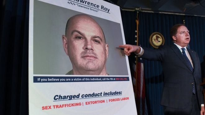 Manhattan US Attorney Geoffrey Berman points at a photo of Lawrence Ray as charges are announced in New York City in February 2020.