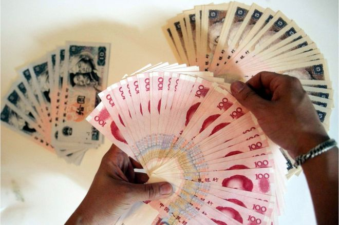 A man lays out the various denominations of the Chinese yuan, in Beijing 8 June 2005.