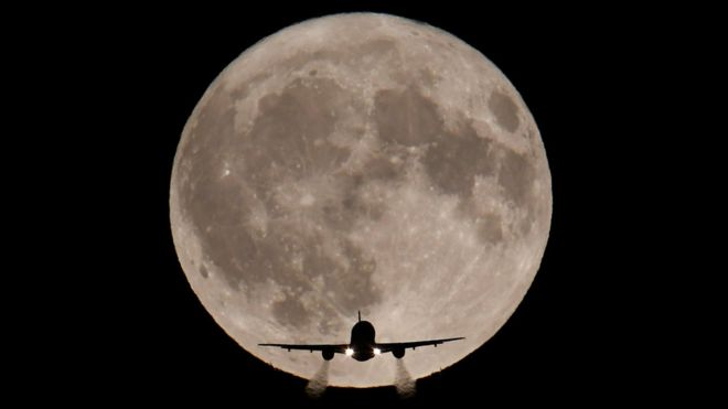 An aeroplane seen in front of the moon
