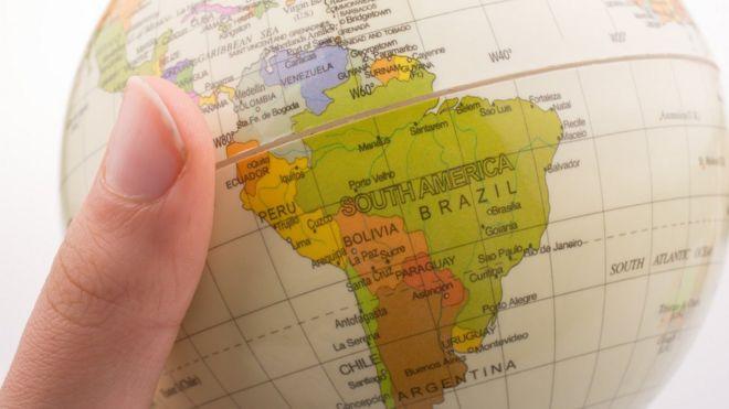 Mano de mujer agarrando globo terráqueo con el mapa de Sudamérica.