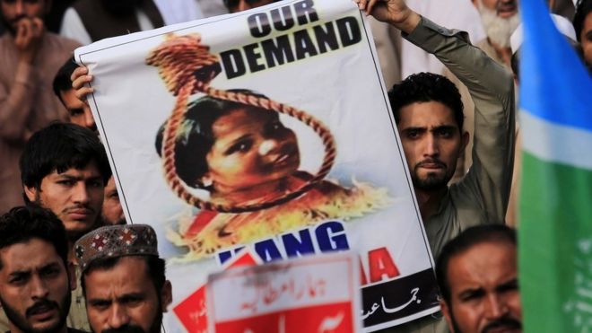 A protester holds up a poster with Asia Bibi's head in a noose above a fire pit