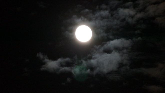 Bright moon shining with clouds