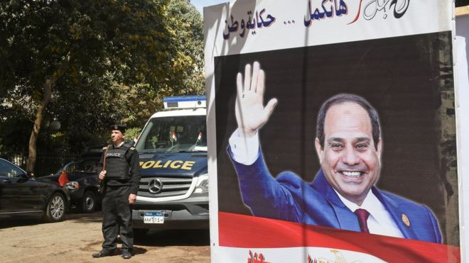 Egyptian policemen                  standing next to an electoral banner depicting President                  Abdel Fattah al-Sisi in the capital Cairo. March 26,                  2018