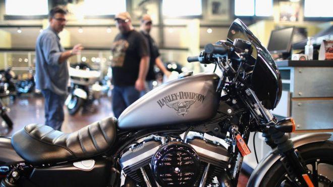 Dos hombres observan una motocicleta Harley-Davidson.