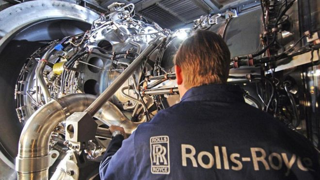 A Rolls-Royce employee working on an engine