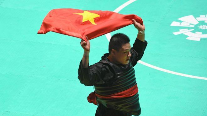 Pesilat Vietnam Van Tri Nguyen membawa bendera usai mengalahkan pesilat Malaysia Moh Khaizul Yaacob dalam babak final Kelas J Putra Asian Games 2018 di Padepokan Pencak Silat Taman Mini Indonesia Indah (TMII), Jakarta, Rabu (29/8).