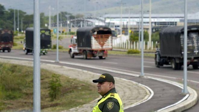 Caminhões com ajuda humanitária passam por um policial colombiano na ponte Tienditas, na fronteira entre a Colômbia e a Venezuela. Foto: 7 de fevereiro de 2019