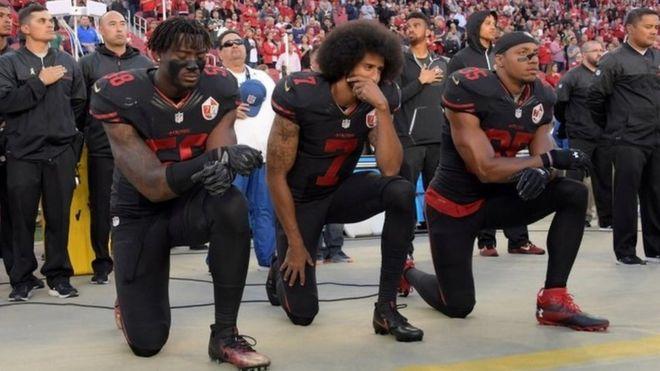 San Francisco 49ers outside linebacker Eli Harold (58), quarterback Colin Kaepernick (7) and free safety Eric Reid (35) kneel during the US national anthem
