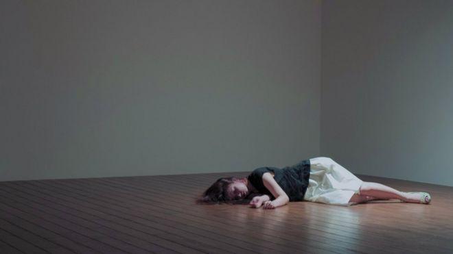 Un mujer yace en el piso de una habitación vacía