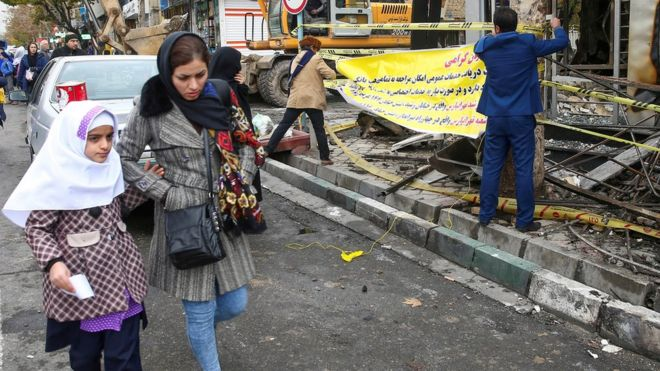 Woman and child walk past debris following anti-government protests in Tehran (20/11/19)