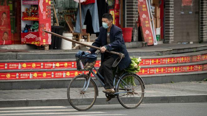 Un hombre en bicicleta con mascarilla en las calles de Wenzhou, China