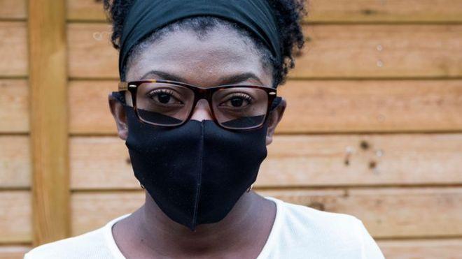 Foto do rosto de uma mulher, que usa uma máscara preta