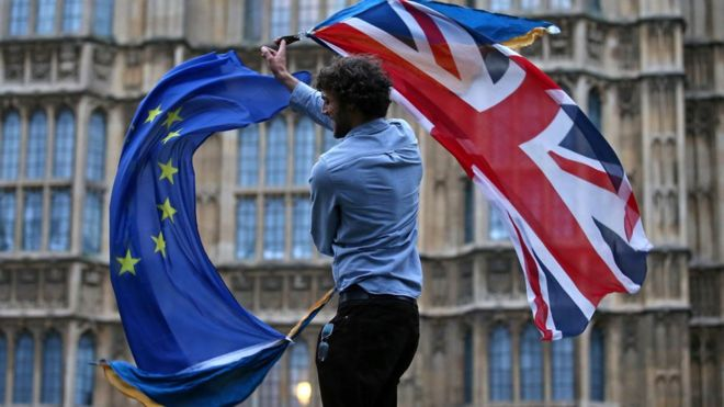A man waves both a Union Jack and an Eu flag