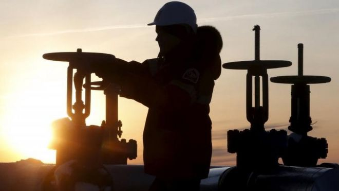 A worker checks the valve of an oil pipe