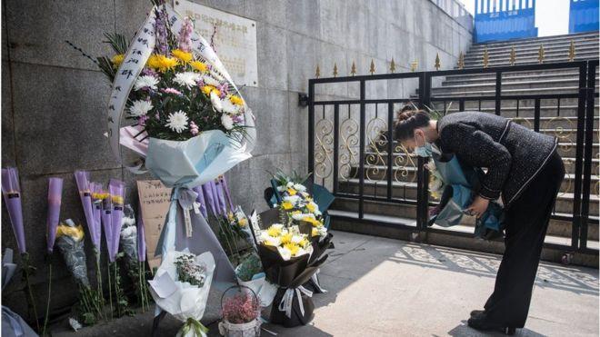 Mujer rinde homenaje a vícitmas del covid-19 en Wuhan