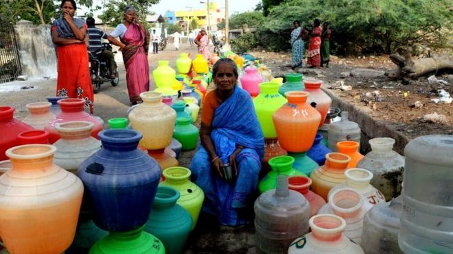 A woman sits amid empty water pots