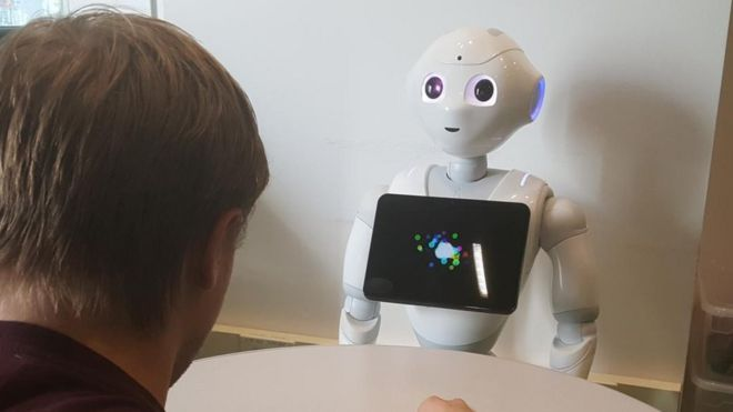 Robot holding screen in front of human