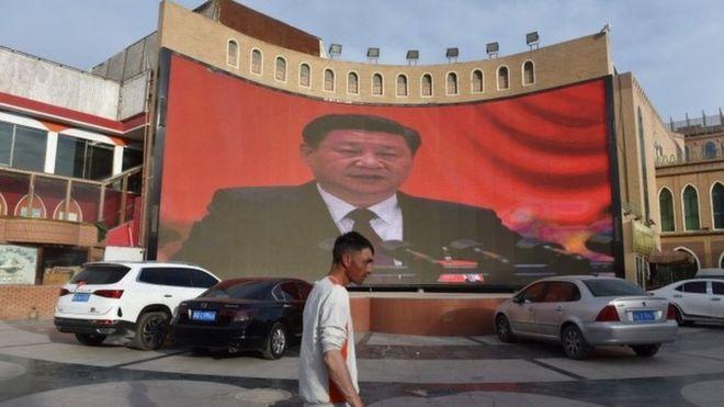 Bir adam Xinjiang Çin Cumhurbaşkanı Xi Jinping görüntülerini gösteren bir ekran yürür