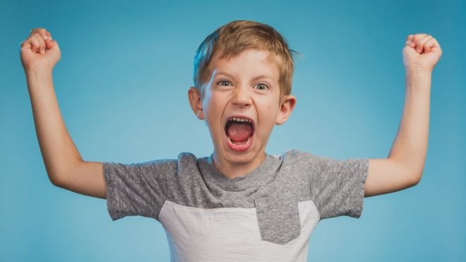 Niño con brazos en alto gritando.