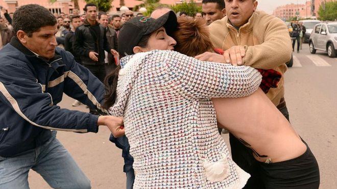 Policías encubiertos arrestando a una activista mientras esta manifestaba frente a la corte de Beni Mellal, durante la audiencia de un juicio de un hombre acusado de ser homosexual.