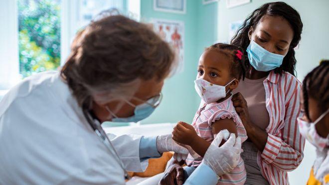 Criança sendo vacinada junto da mãe
