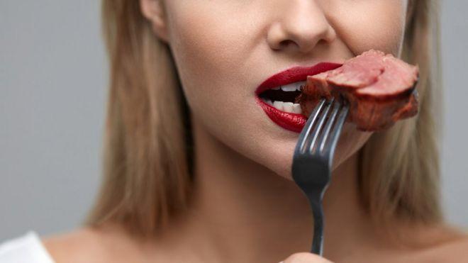 Una mujer con un trozo de carne en la boca.