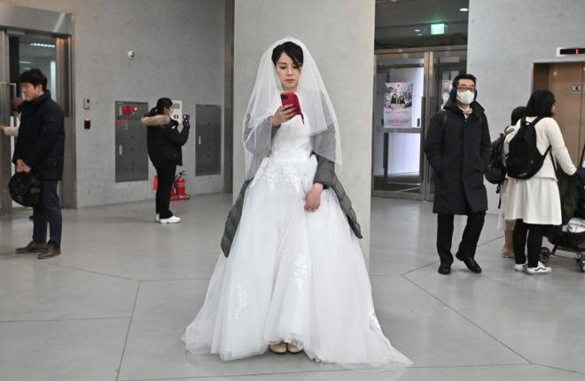 """العروس تأخذ صورة شخصية """"سيلفي"""" في حفل زفاف جماعي نظمته كنيسة التوحيد في كوريا الجنوبية."""