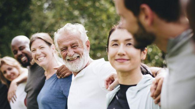 Grupo de seis pessoas em jardim sorri olhando entre si