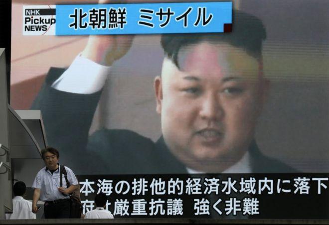 """Un hombre camina en Tokio ante una pantalla con la cara del líder norcoreano Kim Jong-un y que reporta el anuncio que hizo Corea del Norte sobre el """"exitoso"""" lanzamiento de un misil balístico """"intercontinental"""" el 4 de julio de 2017."""
